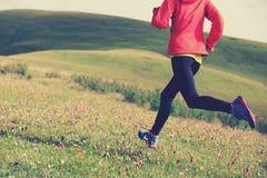 Fitness woman runner running on grassland mountain top Stock Photos