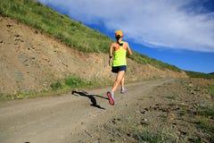 Woman runner running on mountain trail Stock Photo