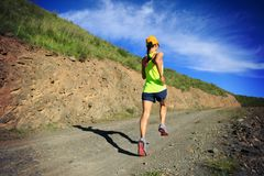 Woman runner running on mountain trail Royalty Free Stock Images