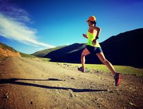 Woman runner running on mountain trail Royalty Free Stock Photo