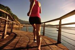 Woman runner running on sunrise seaside boardwalk. Young fitness woman runner running on sunrise seaside boardwalk Royalty Free Stock Image