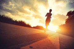 Young fitness woman runner running. On sunrise trail stock photo