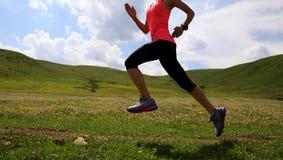 Fitness woman runner running on sunset grassland trail. Young fitness woman runner running on sunset grassland trail Royalty Free Stock Photography