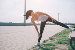 Young fitness woman runner stretching legs before run stock images
