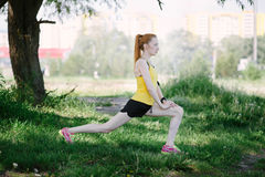 Young fitness woman runner stretching legs before run. Royalty Free Stock Images
