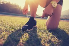 Woman runner tying shoelace on stadium grass royalty free stock images