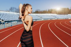 Young fitness woman runner warm up before running on track. Morning exercises at summer stock image