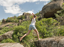 Young fitness woman running barefoot at mountain rocks. Young caucasian beautiful fitness woman running barefoot at mountain rocks Royalty Free Stock Photos