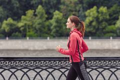 Young fitness woman running in the city park. Handsome young fitness woman running in the city park in the morning Stock Image