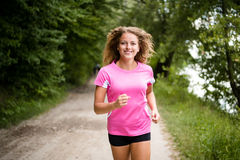 Young fitness woman running through the forest Stock Photos