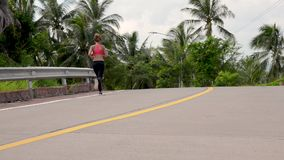 Fitness woman running at tropical forest trail. Young fitness woman running at forest trail stock video