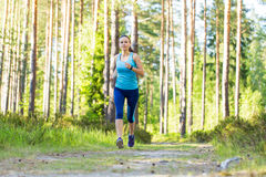 Young fitness woman running in forest trail. Stock Photography