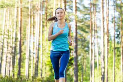 Young fitness woman running in forest trail. Royalty Free Stock Photography