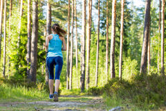 Young fitness woman running in forest trail. Royalty Free Stock Image