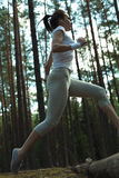 Young fitness woman running and jumping over logs while on extreme outdoor fitness training in forest. Stock Image