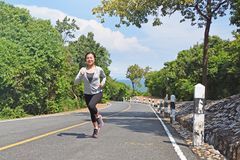 Young fitness woman running on mountain road Royalty Free Stock Image