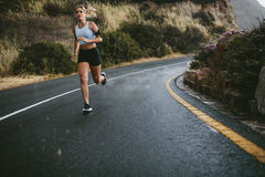 Young fitness woman running outdoors Stock Image