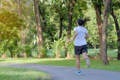 Young fitness woman running in the park outdoor, female runner walking on the road outside, asian athlete jogging and exercise on. Footpath in sunlight morning royalty free stock image
