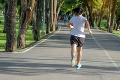 Young fitness woman running in the park outdoor, female runner walking on the road outside, asian athlete jogging and exercise on. Footpath in sunlight morning stock photo