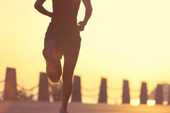 Young fitness woman running on sunrise seaside Stock Photo