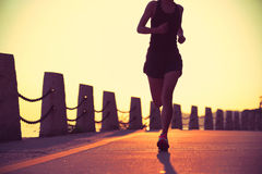 Young fitness woman running on sunrise seaside Royalty Free Stock Image