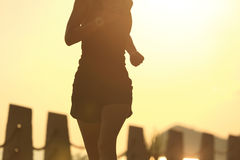 Young fitness woman running on sunrise seaside Royalty Free Stock Photos