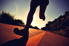 Young fitness woman running on sunrise seaside trail Stock Images
