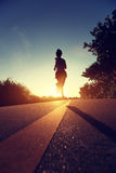 Young fitness woman running on sunrise seaside trail Royalty Free Stock Photos