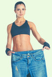 Young fitness woman showing that her old jeans Stock Image