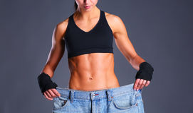 Young fitness woman showing that her old jeans Royalty Free Stock Images