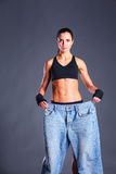 Young fitness woman showing that her old jeans Stock Photo