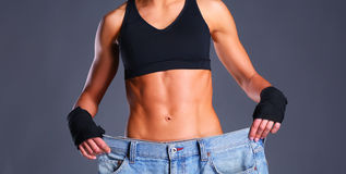 Young fitness woman showing that her old jeans Royalty Free Stock Photography