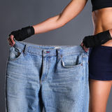 Young fitness woman showing that her old jeans Stock Images