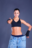 Young fitness woman showing that her old jeans and showing ok Stock Photography
