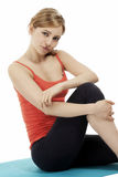 Young fitness woman sitting on a blue mat Royalty Free Stock Photography