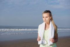 Young fitness woman standing at the beach with towel Stock Images