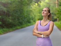Young fitness woman stay in the park with crossed one`s arms Royalty Free Stock Images