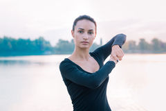 Young fitness woman stretches on pier during workout at dawn stock photos