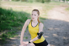 Young fitness woman stretching body before run. Royalty Free Stock Photos