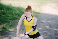 Young fitness woman stretching body before run. Royalty Free Stock Images
