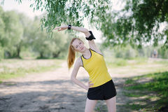 Young fitness woman stretching body before run. Stock Photo