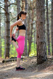 Young Fitness Woman Stretching her Legs in the Pine Forest. Female Runner Doing Stretches . Healthy Lifestyle Concept. Stock Images