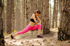 Young Fitness Woman Stretching in the Pine Forest. Female Runner Doing Stretches . Healthy Lifestyle Concept. Stock Photo