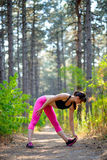 Young Fitness Woman Stretching in the Pine Forest. Female Runner Doing Stretches . Healthy Lifestyle Concept. Stock Image