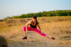 Young Fitness Woman Stretching in the Wild Park. Female Runner Doing Stretches . Healthy Lifestyle Concept. Stock Photography