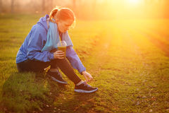Young fitness woman taking a break outside in summer fitness wor Royalty Free Stock Image