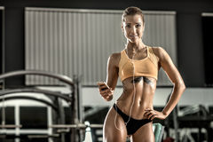 Young fitness woman tired in gym and listen music with headset Stock Photography