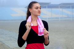 Young fitness woman with towel during workout break outdoor Stock Photos