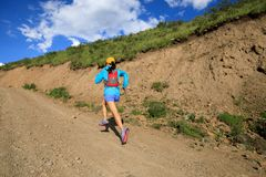 Woman runner running on mountain trail Royalty Free Stock Photography