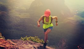 Fitness woman trail runner running up to mountain top. Young fitness woman trail runner running up to mountain top royalty free stock photography